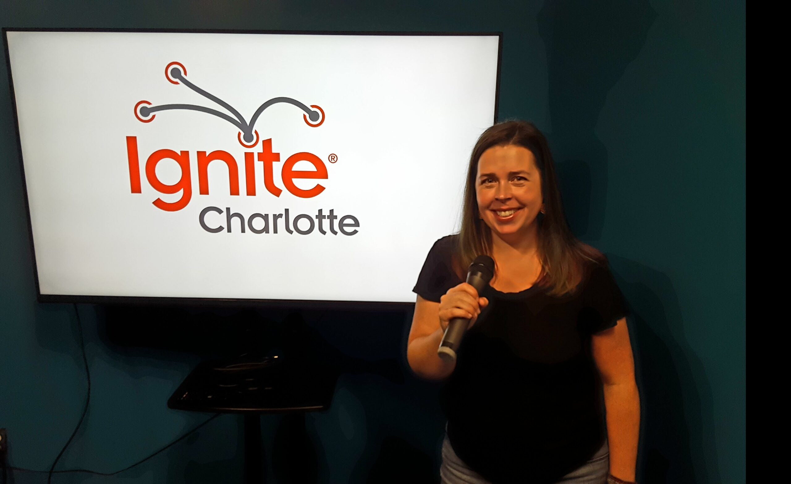 Nicole stands in front of an Ignite Charlotte sign. She is smiling and holding a microphone.